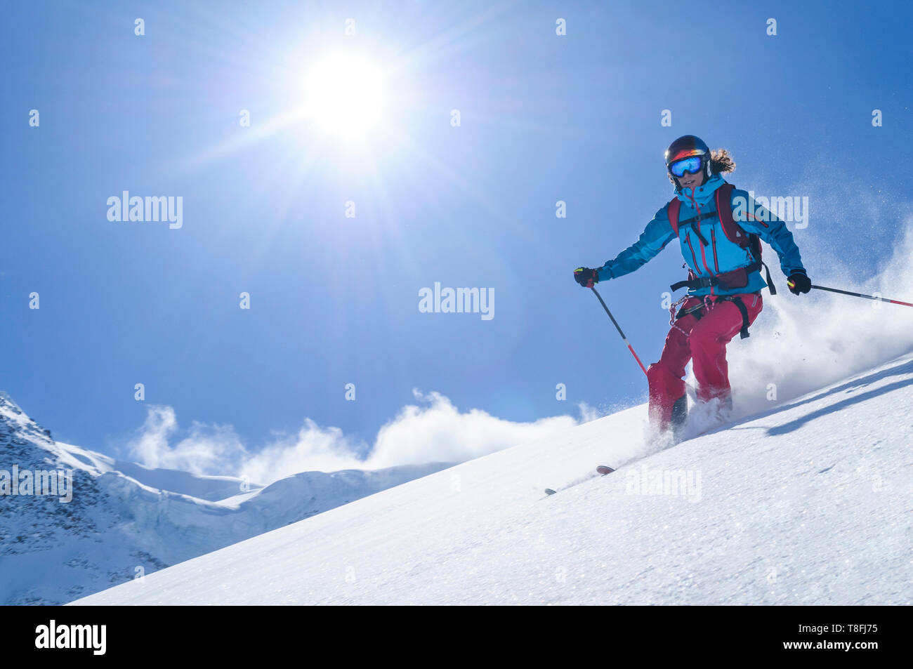 Female freeskier skiing in backcountry on fantastic Monte Rosa glaciers - Stock Image