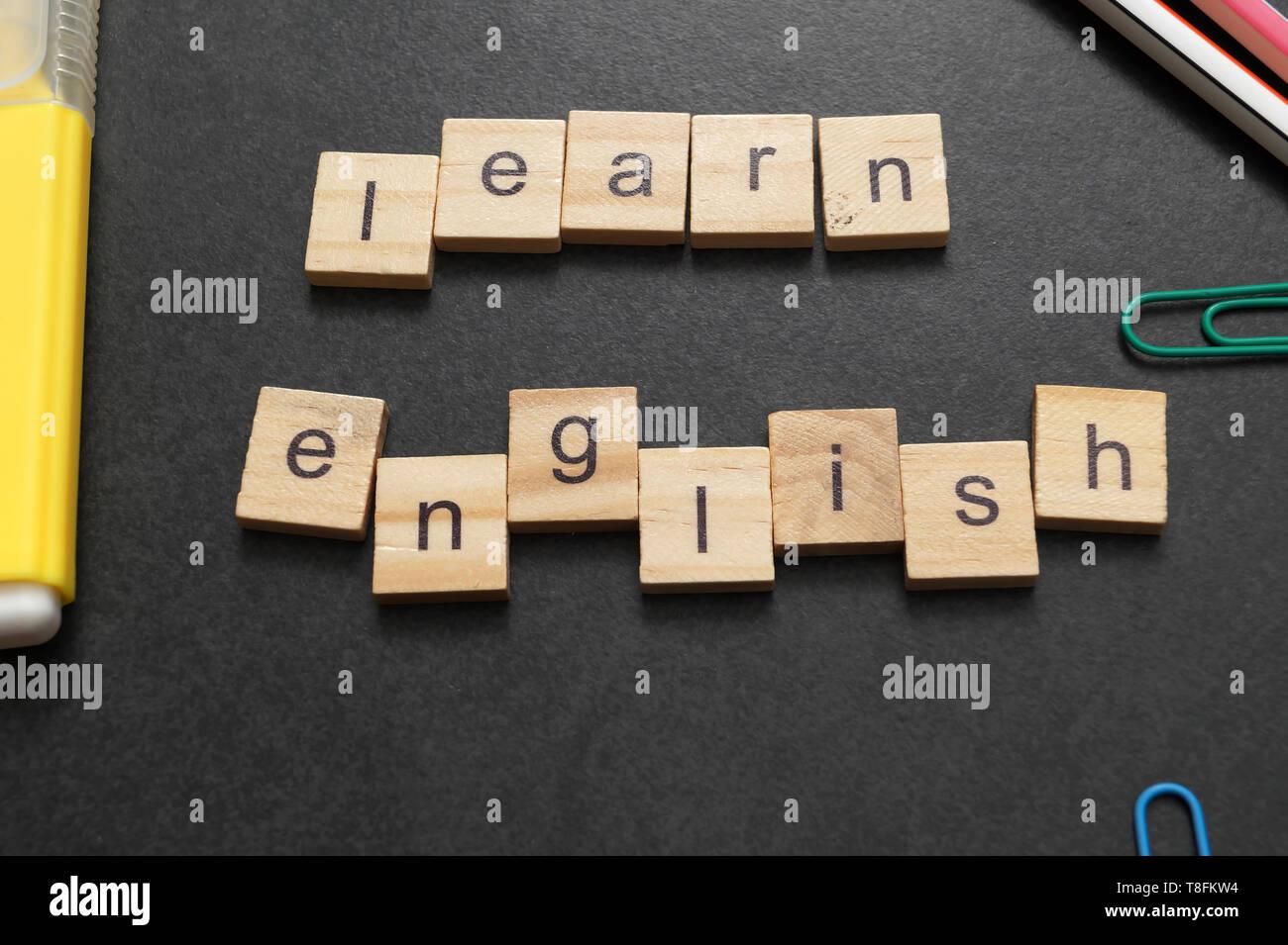 Word LEARN ENGLISH written on wood block. Close up - Stock Image