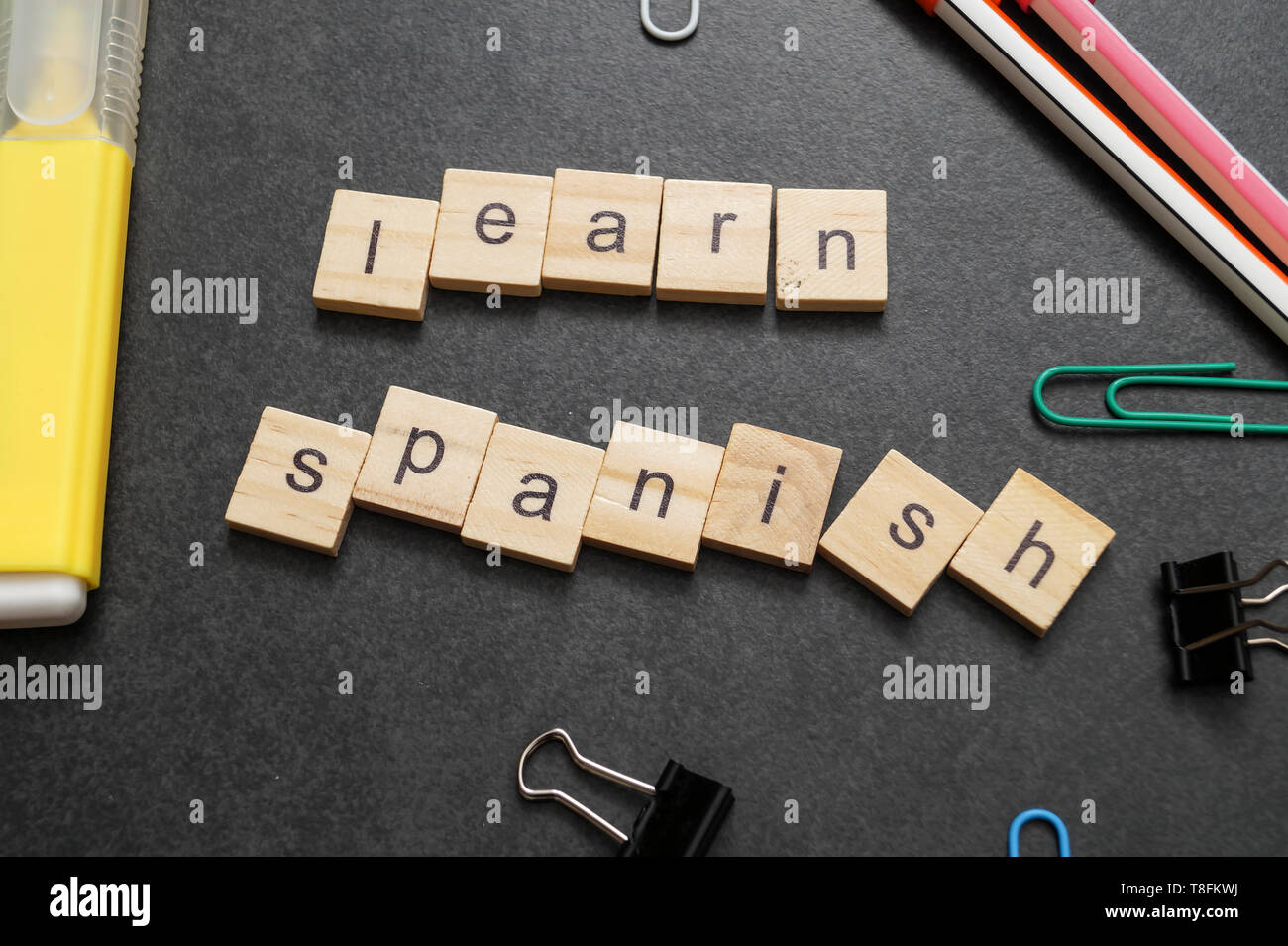 Word LEARN SPANISH written on wood block. Close up - Stock Image