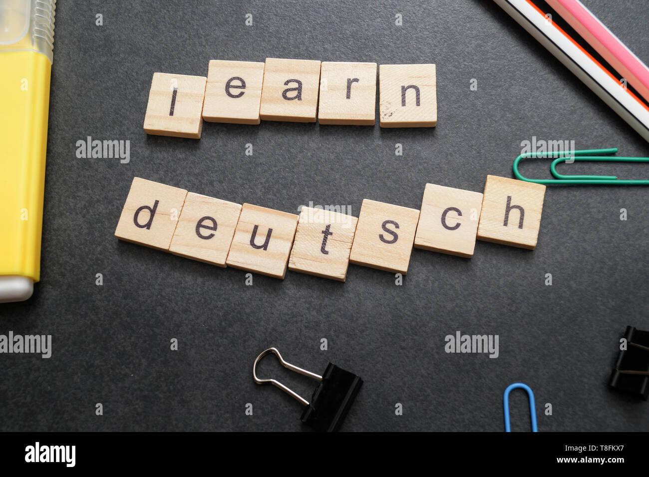 Word LEARN DEUTSCH written on wood block. Close up - Stock Image