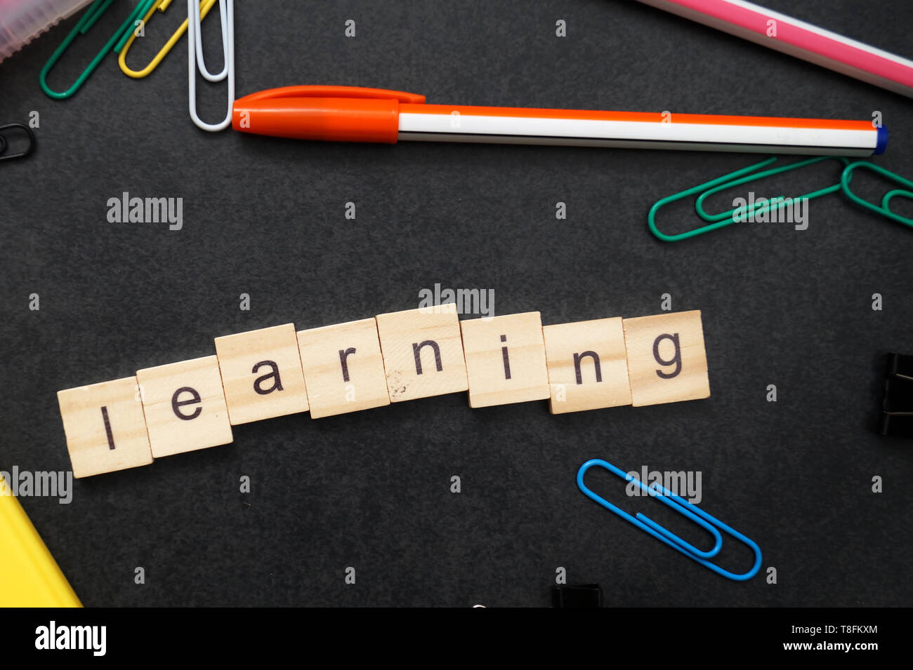 LEARNING word written on wood block, from above - Stock Image