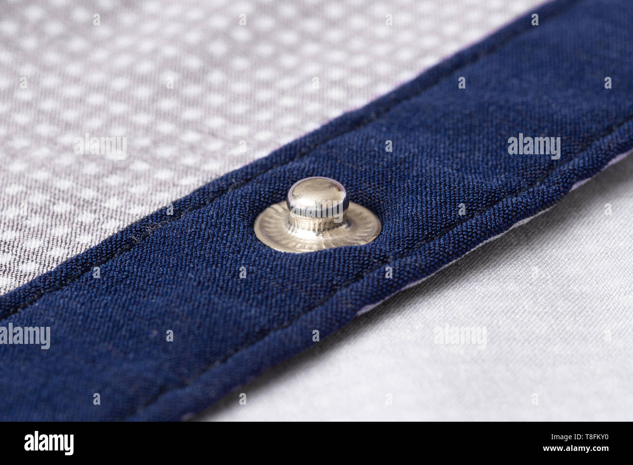 Press-stud (fastener) on blue shirt plank closeup. - Stock Image