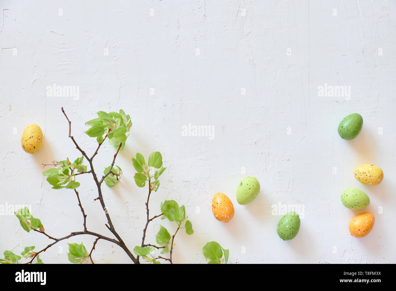Fresh spring lime leaves, green and yellow decorative eggs. Easter flat lay on textured white background, copy-space - Stock Image