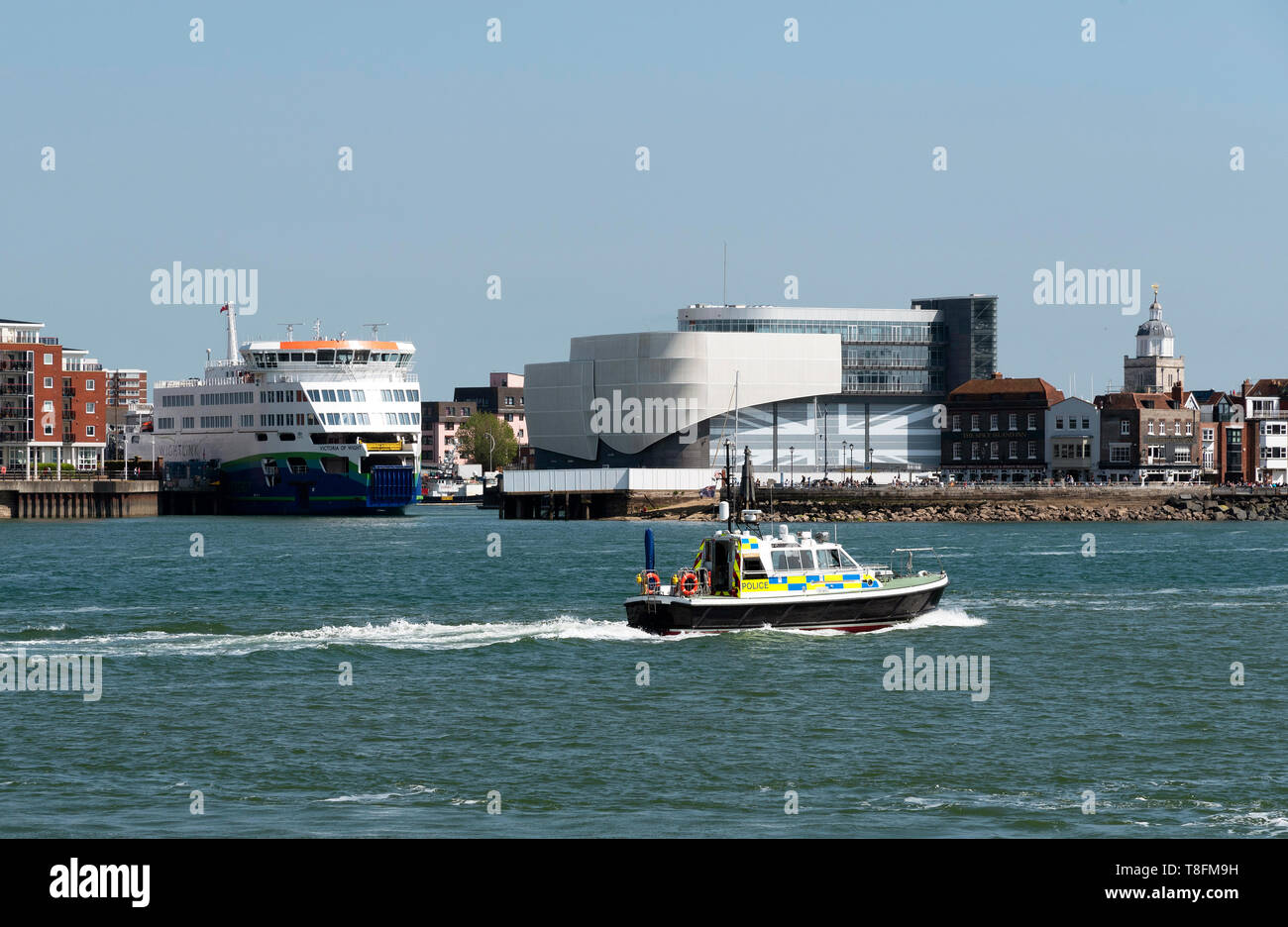 Portsmouth Harbour, England, UK. May 2019. The roro ferry Victoria of Wight passing the Ben Ainslie Racing HQ building. Police boat passing by. Stock Photo