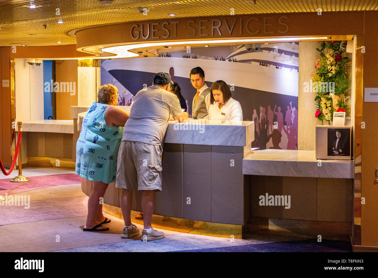 A couple on the cruise ship Eurodam go to the front desk to ask for some help, Hawaii, USA. Stock Photo