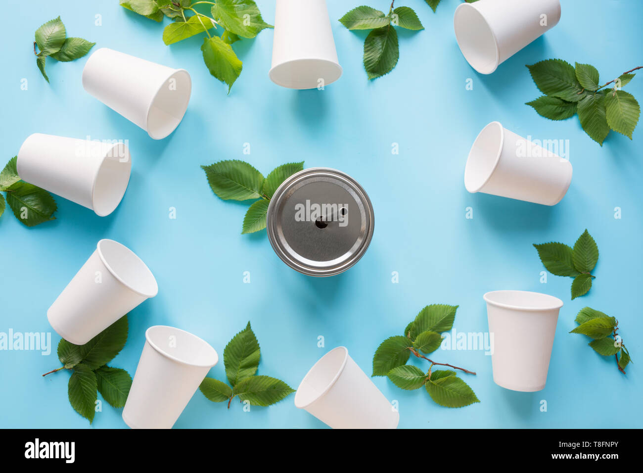 Border of white disposable cup and green leaves on blue background. Save the planet. Zero waste. Top view Stock Photo