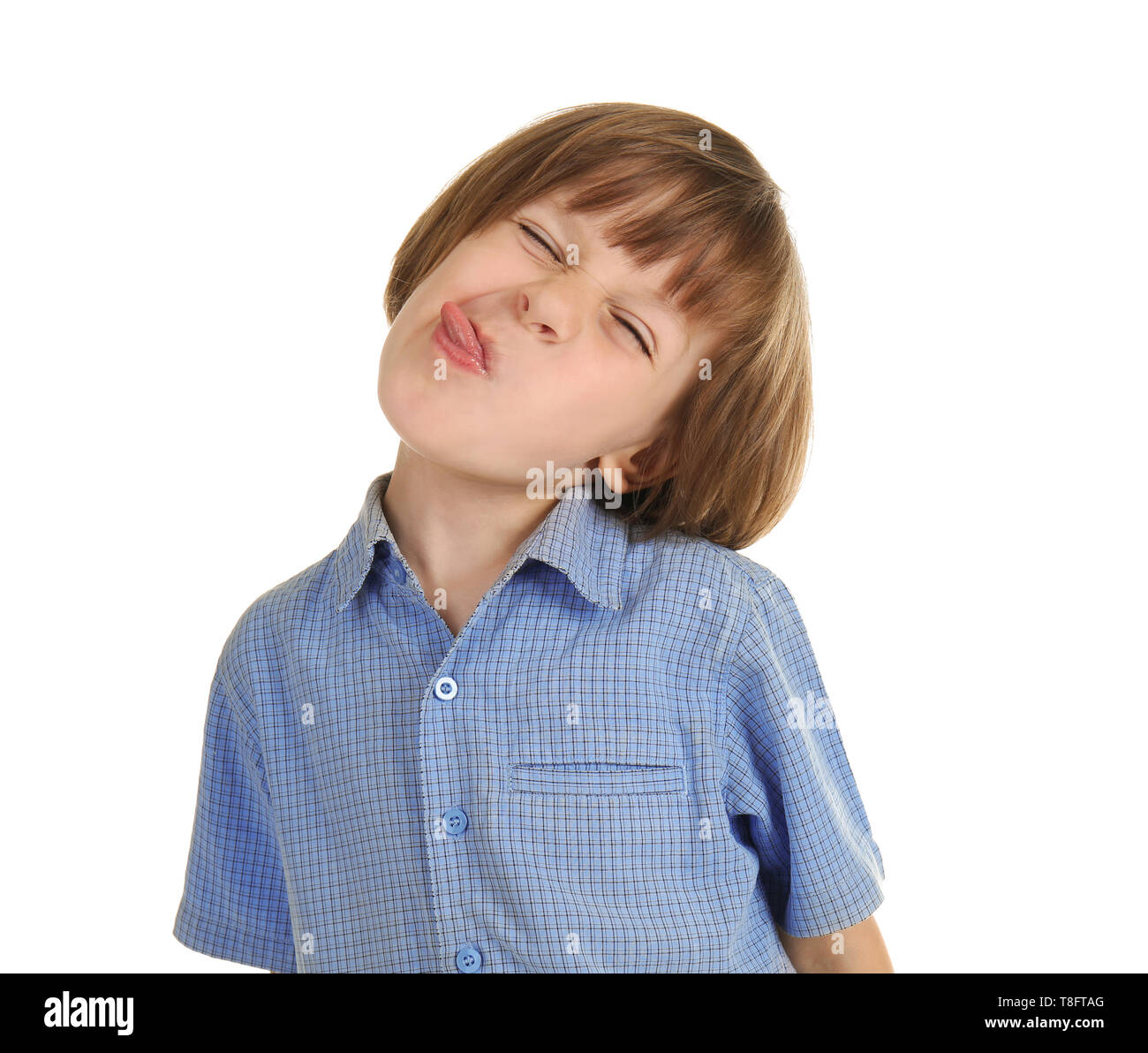 Cute little boy showing tongue on white background - Stock Image