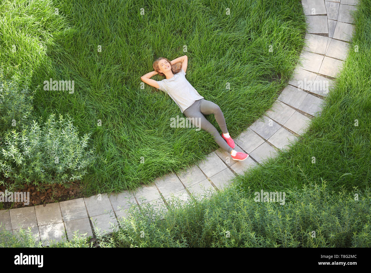 Sporty young woman lying on green grass in park - Stock Image