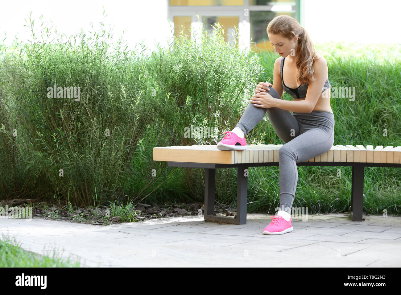 Sporty young woman suffering from knee pain while sitting on wooden bench in park - Stock Image