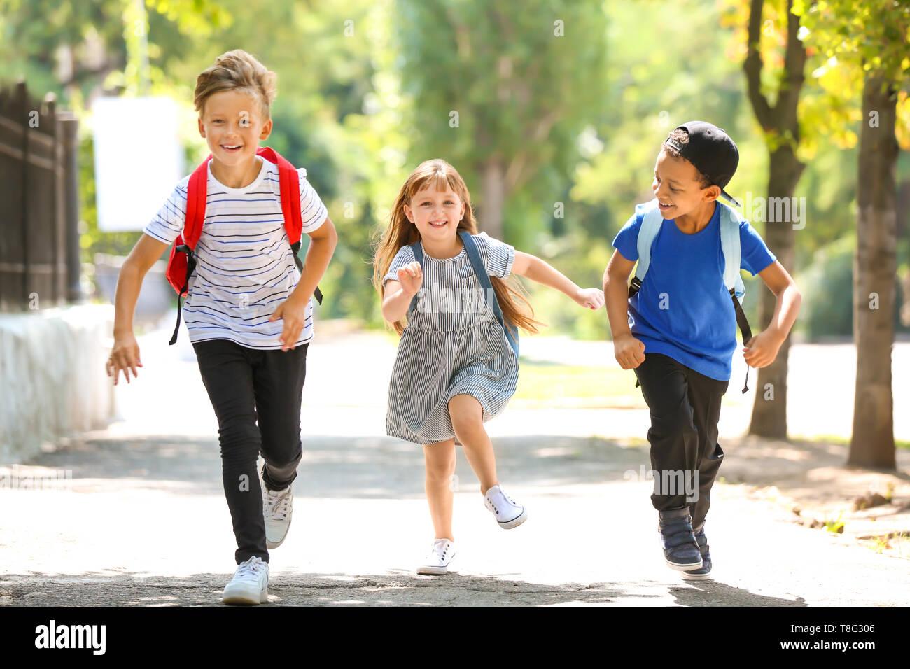 Cute little schoolchildren running outdoors - Stock Image