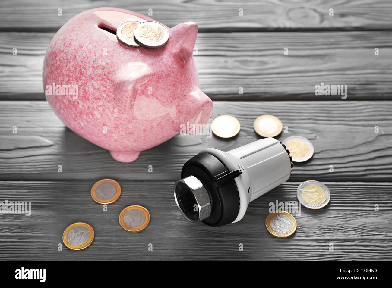 Piggy bank with coins and thermostat on wooden background. Heating saving concept - Stock Image