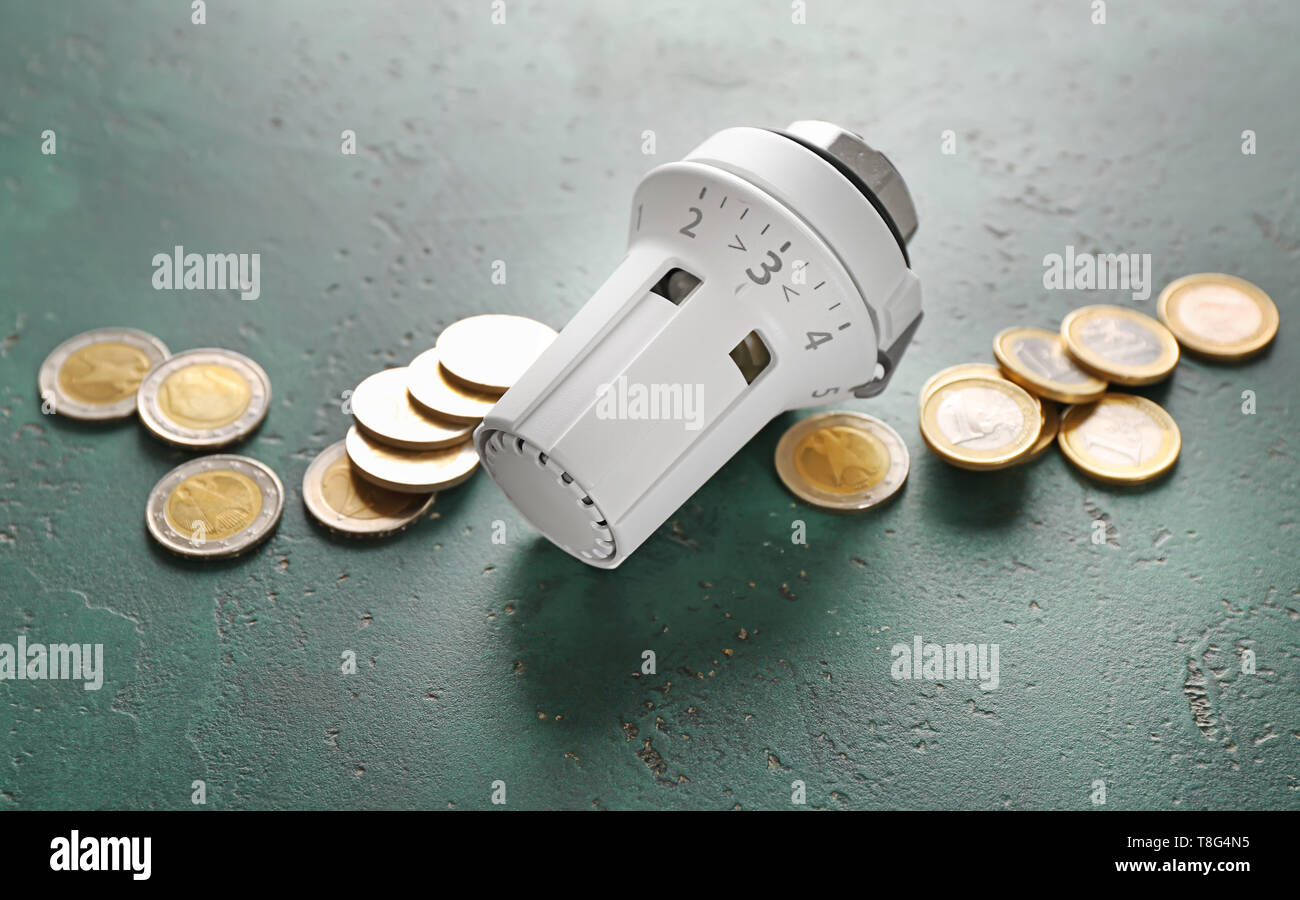 Thermostat with coins on color background. Heating saving concept - Stock Image