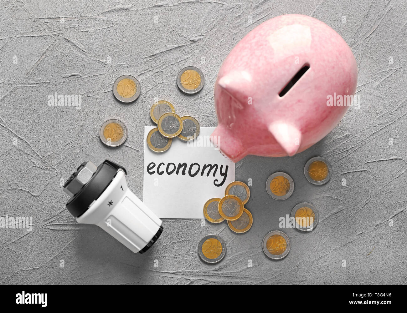 Piggy bank with coins and thermostat on grey background. Heating saving concept - Stock Image