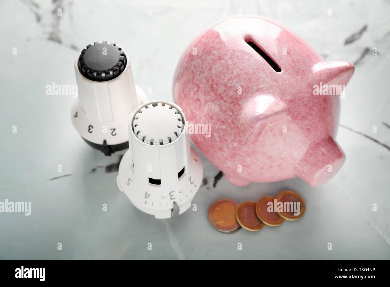Piggy bank with coins and thermostats on light background. Heating saving concept - Stock Image
