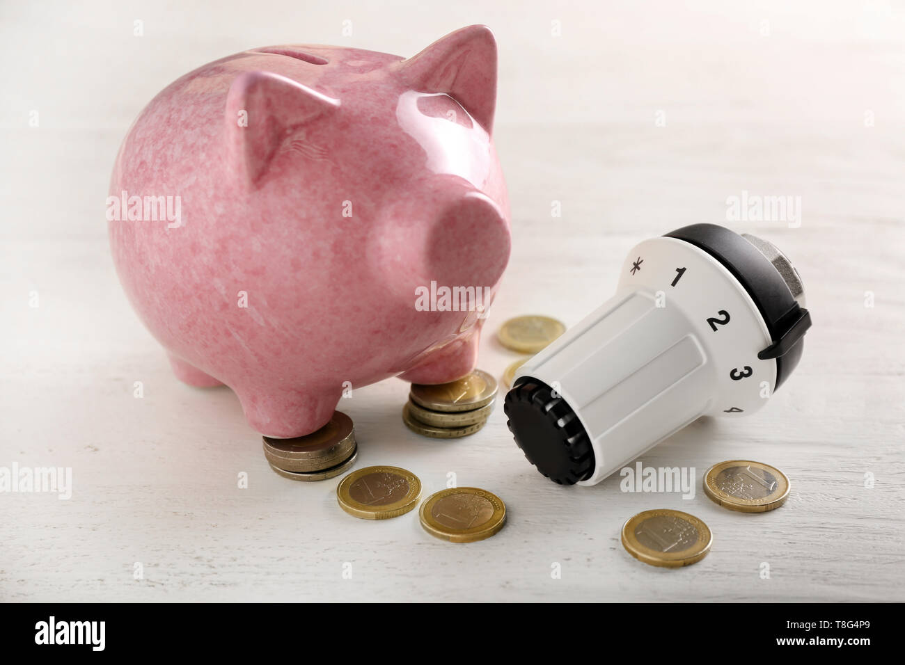 Piggy bank with coins and thermostat on white table. Heating saving concept - Stock Image