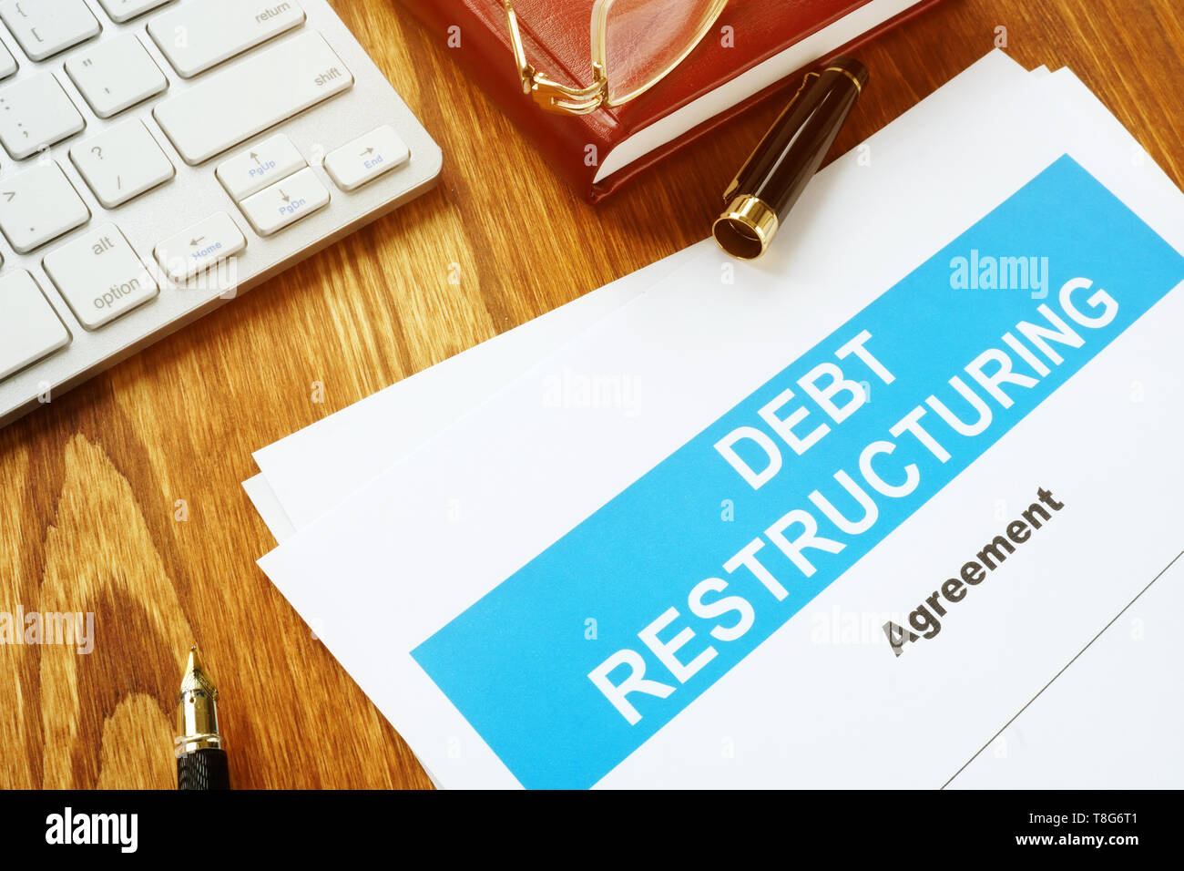 Debt restructuring Agreement DRA with keyboard and pen. - Stock Image