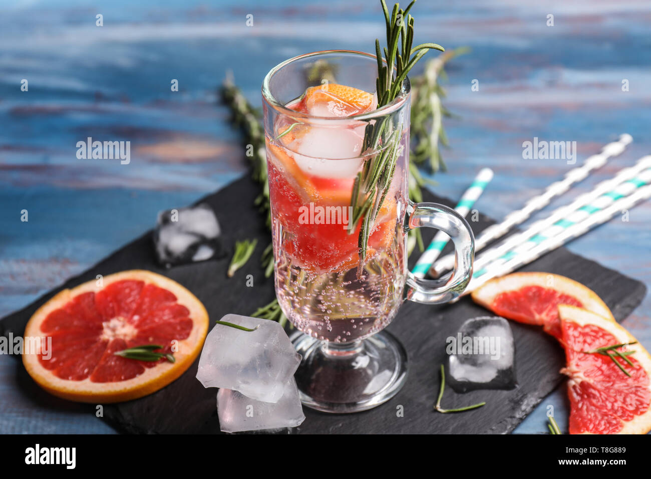 Fresh grapefruit cocktail with rosemary in glass cup on slate plate Stock Photo