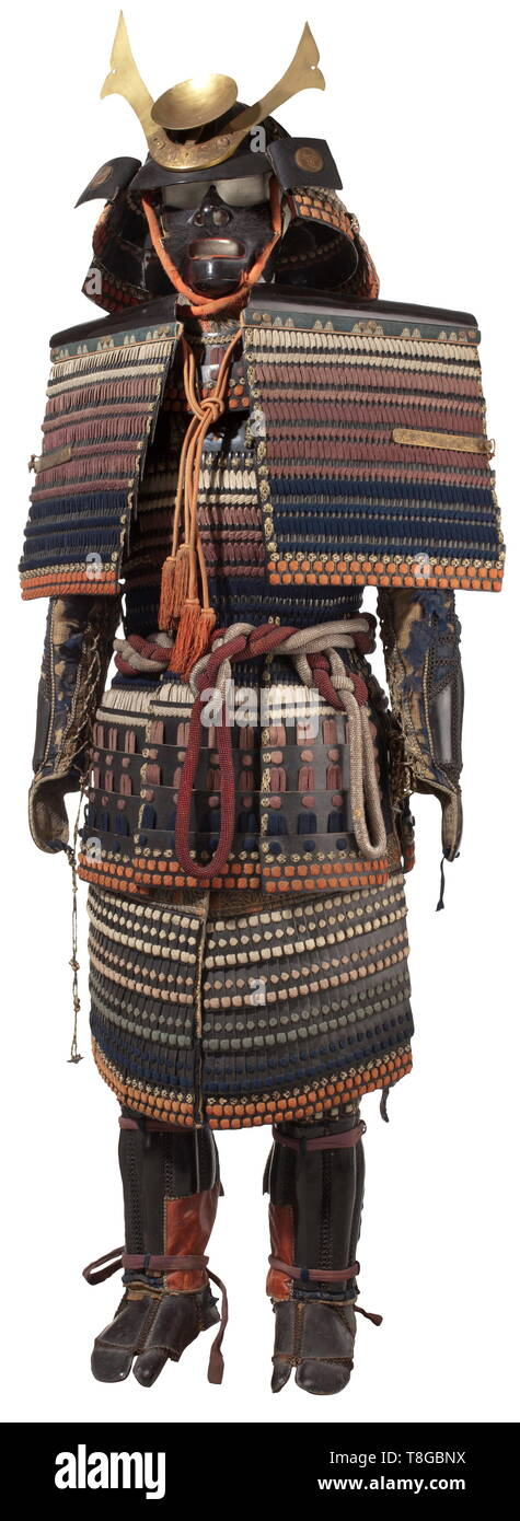 A Japanese warabe gusoku - a boy's armour, beginning of the 20th century O-boshi with three-lame shikoro made from leather and lacquered cardboard, the fukigaeshi with mon in the style of the Mitsutomoe clan. Black-lacquered oiyebo mempo with beard and two-lame yodare kake. Seven-lame o-sode, a pair of tsutsu kote with iyo edging at the upper arm, tekko without thumb and mounted on blue velvet. Do-maru bound in shairo, murrasaki and kon colours and offset by coloured leather. Seven five-lame kusazuri. Goroes agamaki, the inner leather coating is , Additional-Rights-Clearance-Info-Not-Available - Stock Image