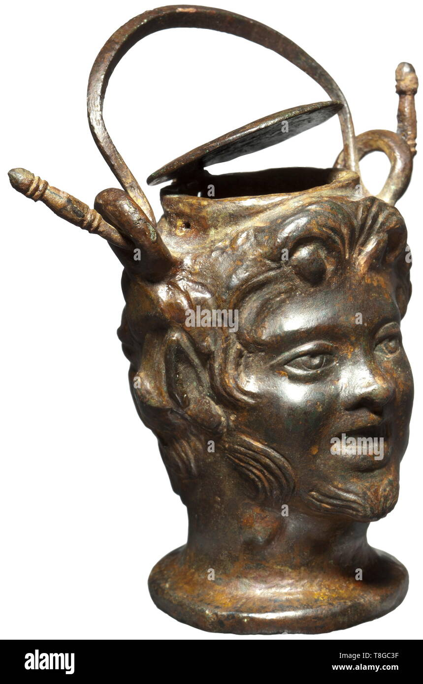 A Roman ointment vessel shaped like a Satyr´s head, 2nd century A.D. Bronze with greenish patina. Vessel shaped like the three-dimensional head of a young Satyr with chin beard, pointed ears and curly hair. Two loops on the side with intact carrying handle, hinged, round lid. Height without handle 9 cm. Provenance: Private collection in the USA, ex Christie´s, New York, 12 December 2002. Before that part of an English private collection since 1978. historic, historical, Roman Empire, ancient world, ancient times, ancient world, Additional-Rights-Clearance-Info-Not-Available - Stock Image