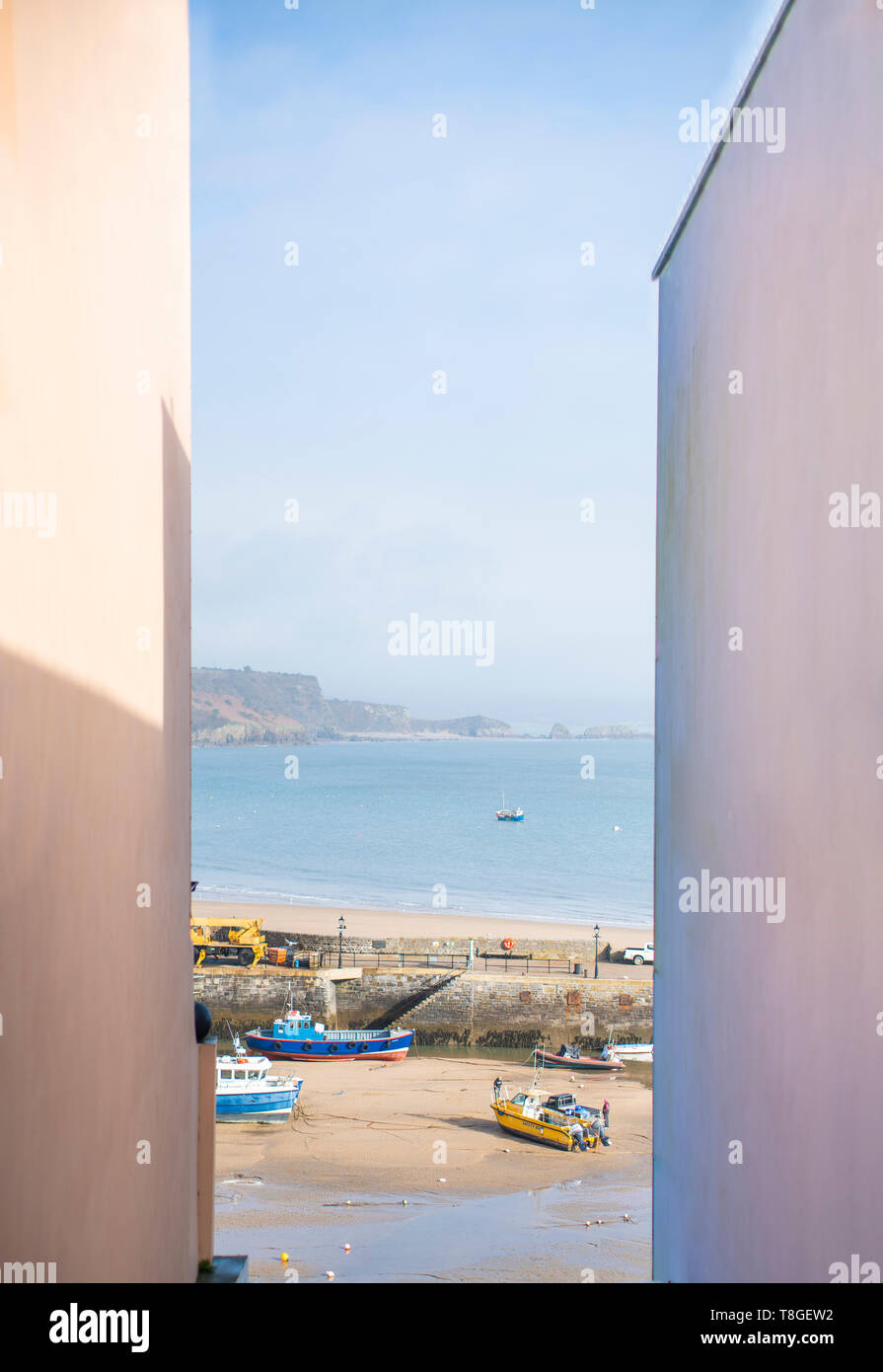 A view of the sea between two buildings in Tenby, South Wales, on a sunny day. - Stock Image