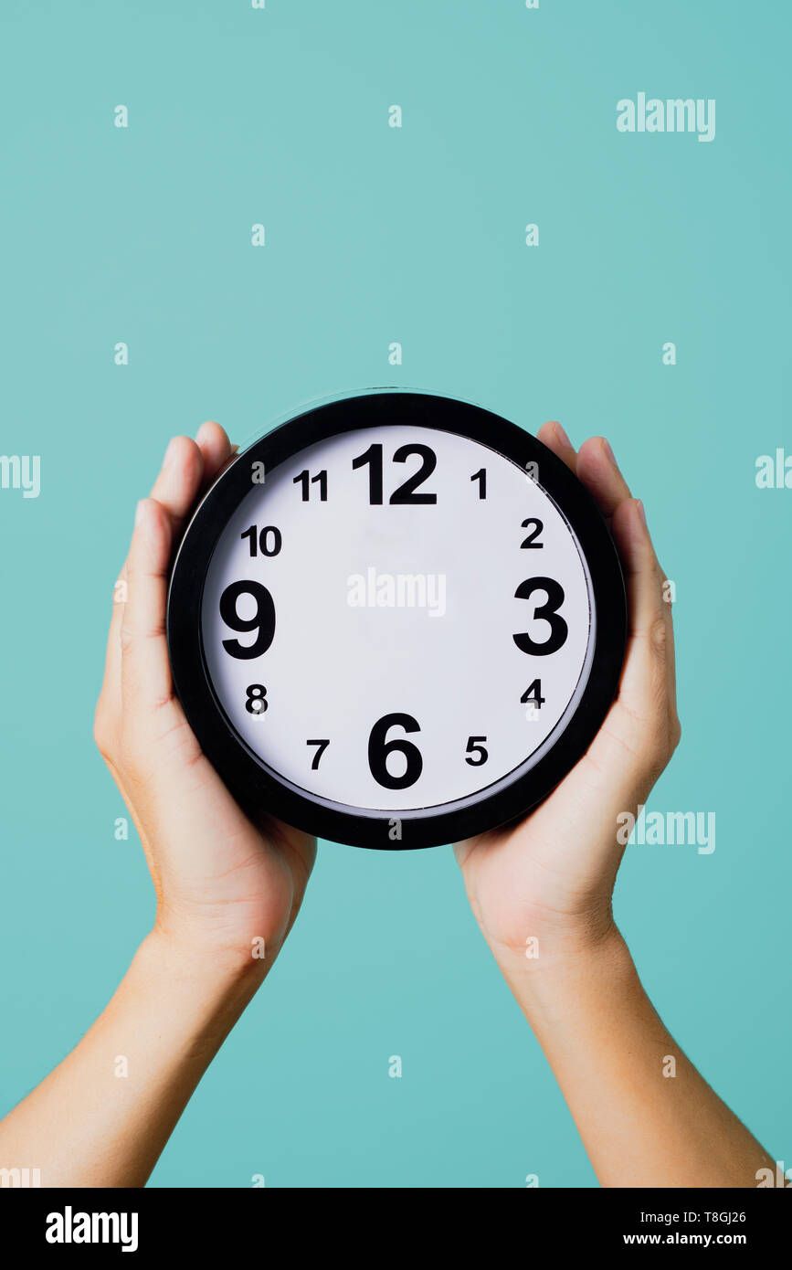the hands of a young caucasian man holding a clock, without hour or minute hands, against a blue background, depicting concepts such as to not have ti - Stock Image