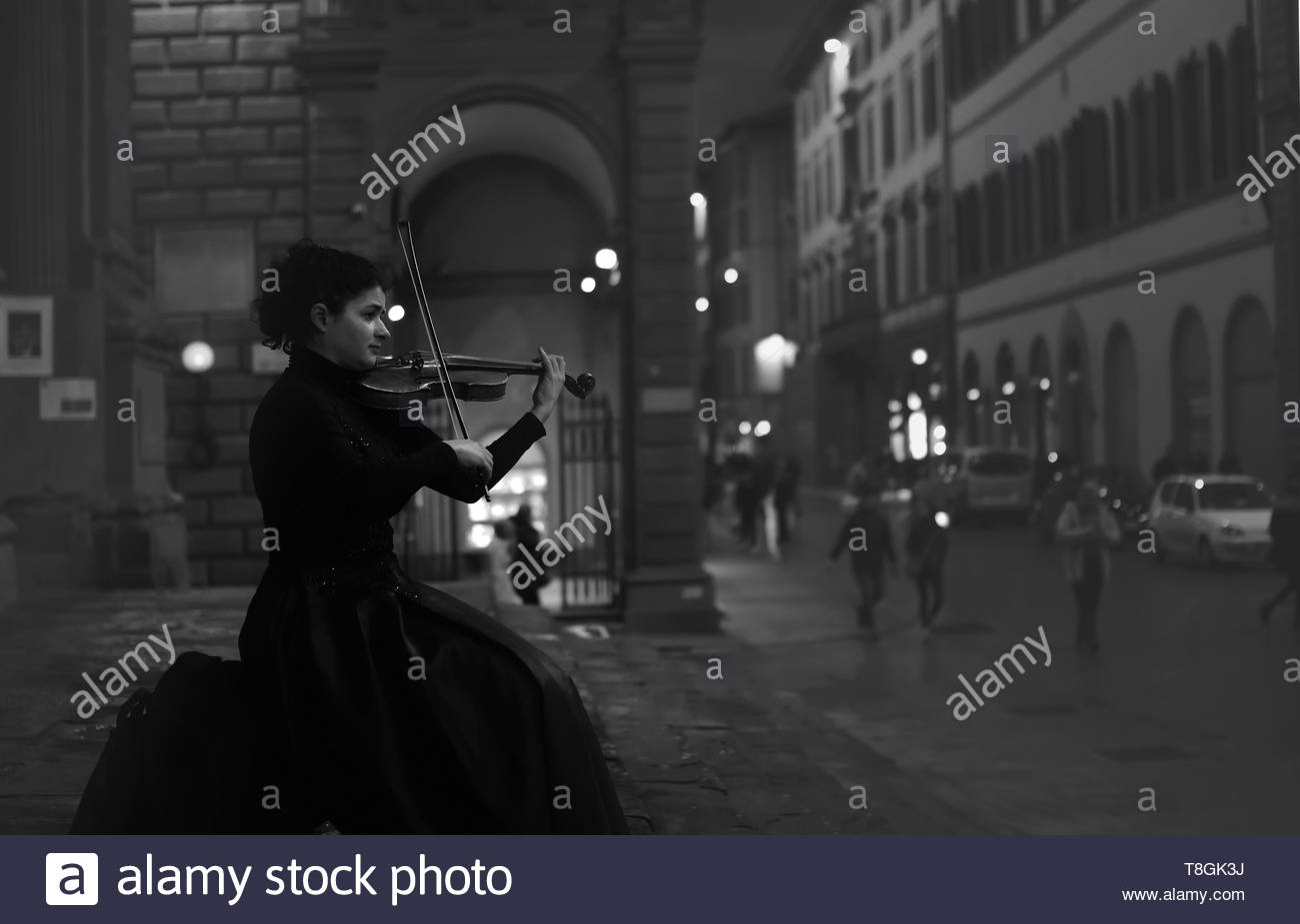 Florence by night. A street artist plays his violin. In the background a famous downtown street. Black and white photos. - Stock Image