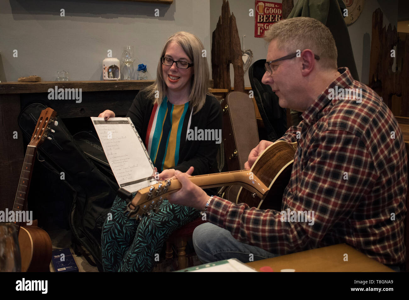 Memory loss cant remember the word and music to a folk song. Girl friend helping out by  holding the music score, song sheet Halifax pub Yorkshire 2010s 2019 UK HOMER SYKES - Stock Image