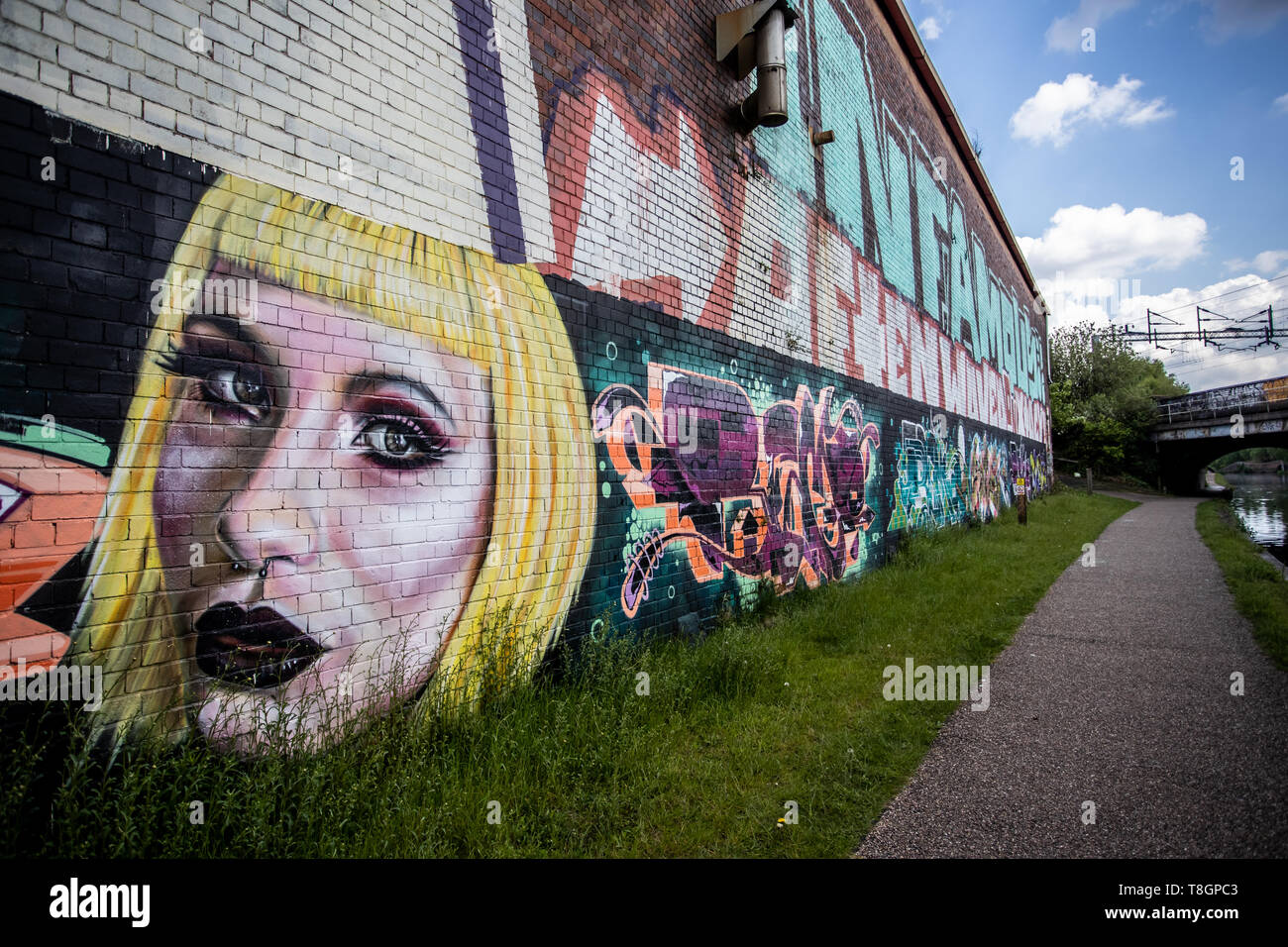 Graffiti along the towpath of the canal in Smethwick, Birmingham, UK - Stock Image