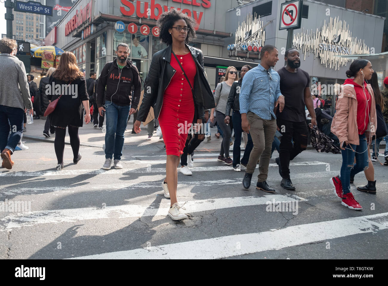 A diverse group of pedestrians on 8th Avenue crossing West 34th Street near Penn Station in Manhattan. Stock Photo