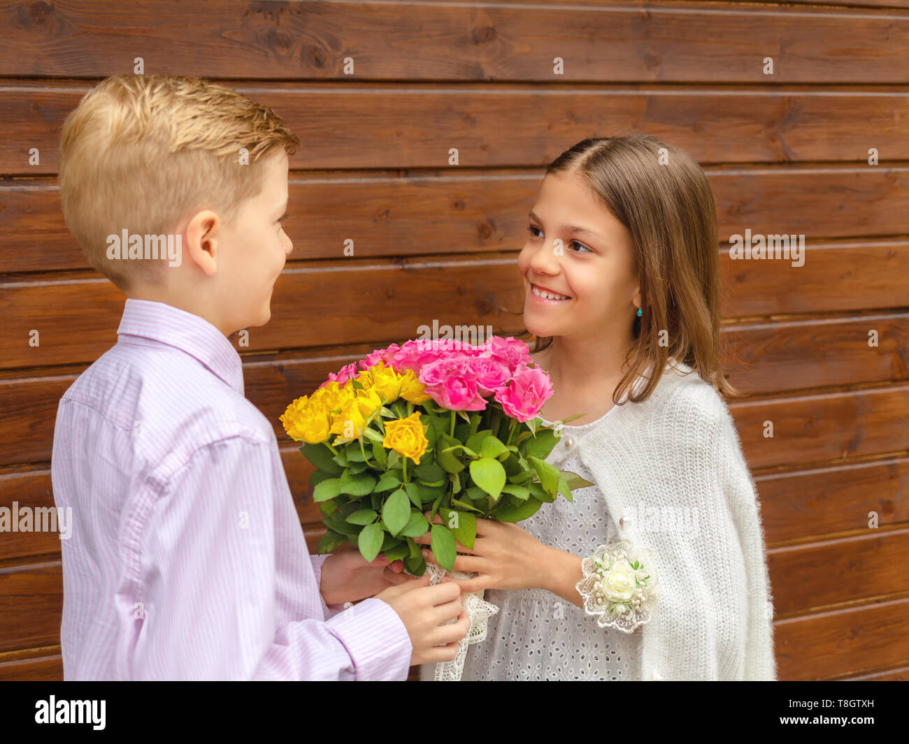 Cute little boy giving bouquet of flowers to charming little lady – smiling girl in love receiving yellow and pink roses from friend – generation z - Stock Image
