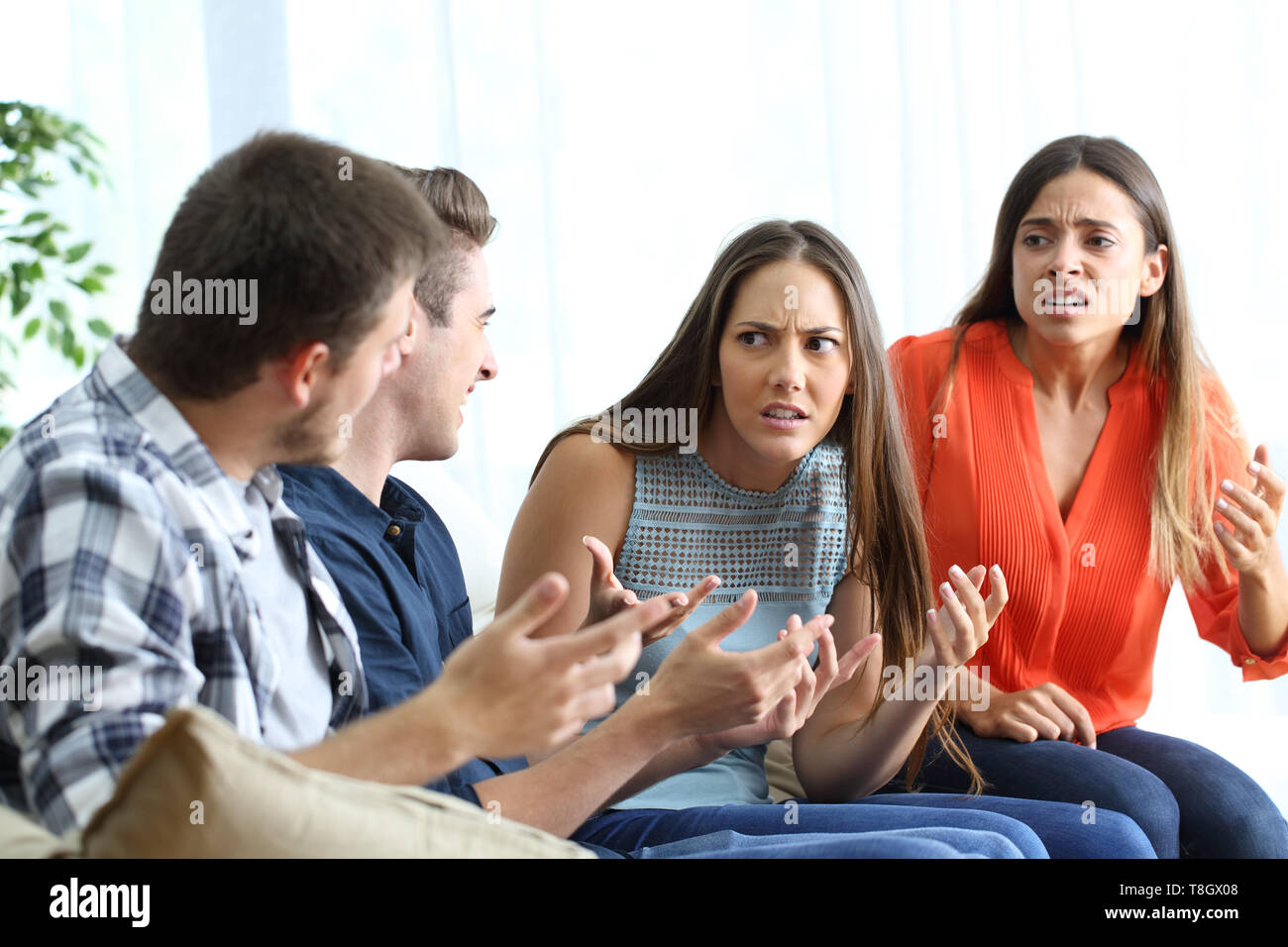 Four angry friends fighting sitting on a couch at home - Stock Image