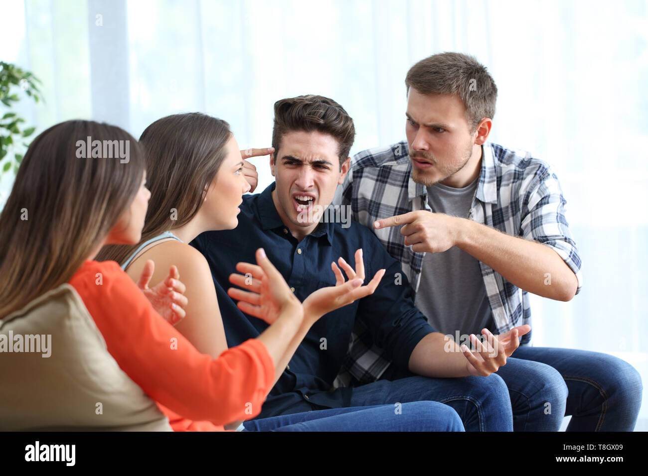 Four angry friends arguing accusing each others at home - Stock Image