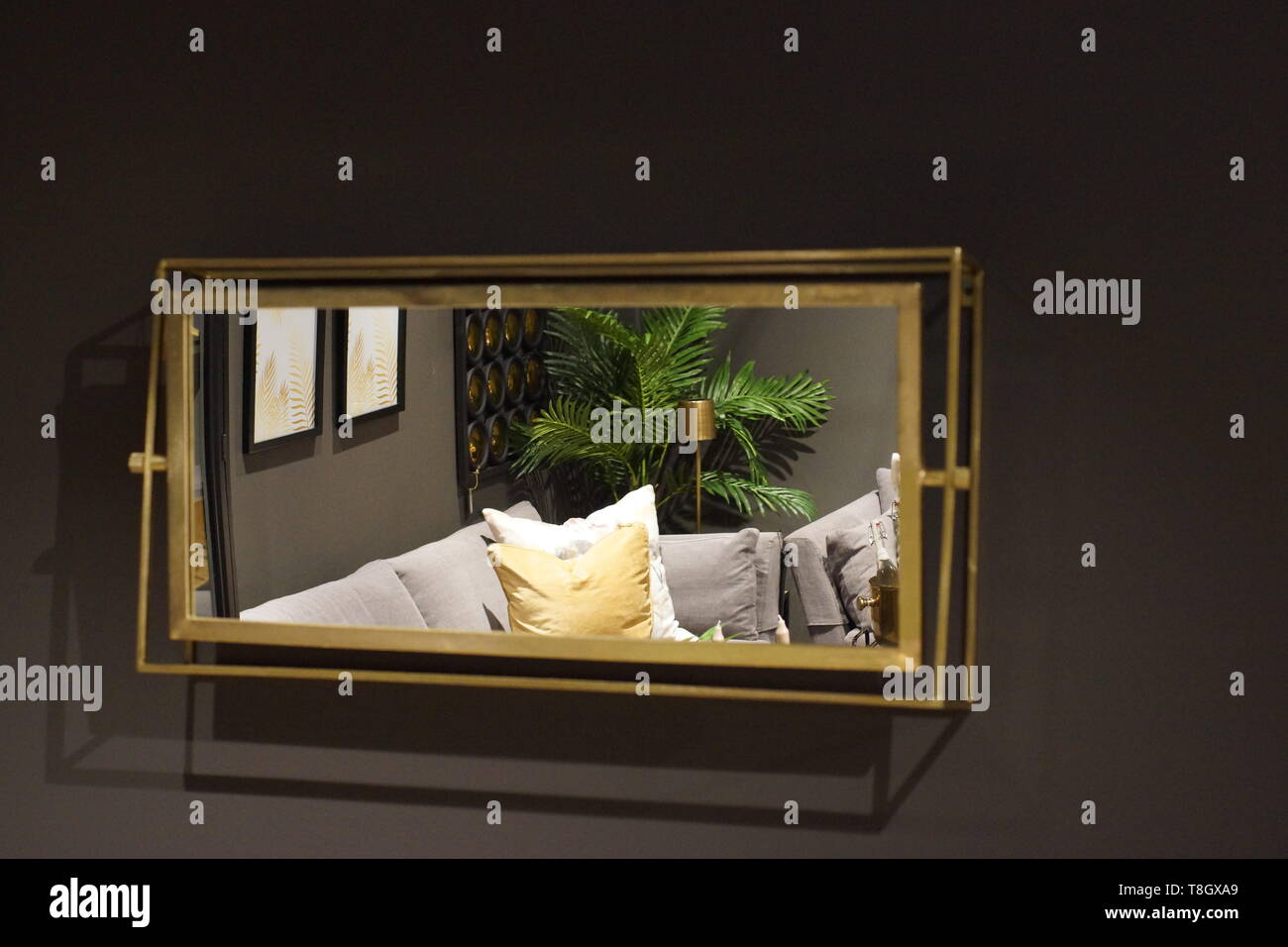 On the gray wall hangs a rectangular mirror, which reflects the room with furniture Stock Photo
