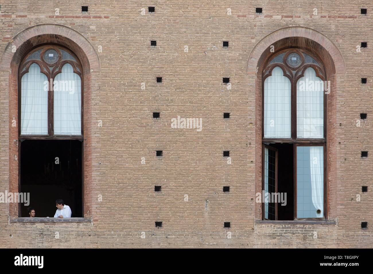 Italy, Tuscany, Sienna, historical center listed as World Heritage by UNESCO, people by a window of the Palazzo Pubblico on Piazza Mercato (market square) - Stock Image