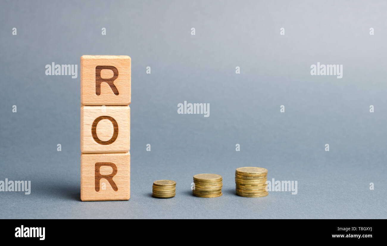 Wooden blocks with the word ROR and coins. High level of business profitability. Return on investment, invested capital, rate. Success. Growth. Profit Stock Photo