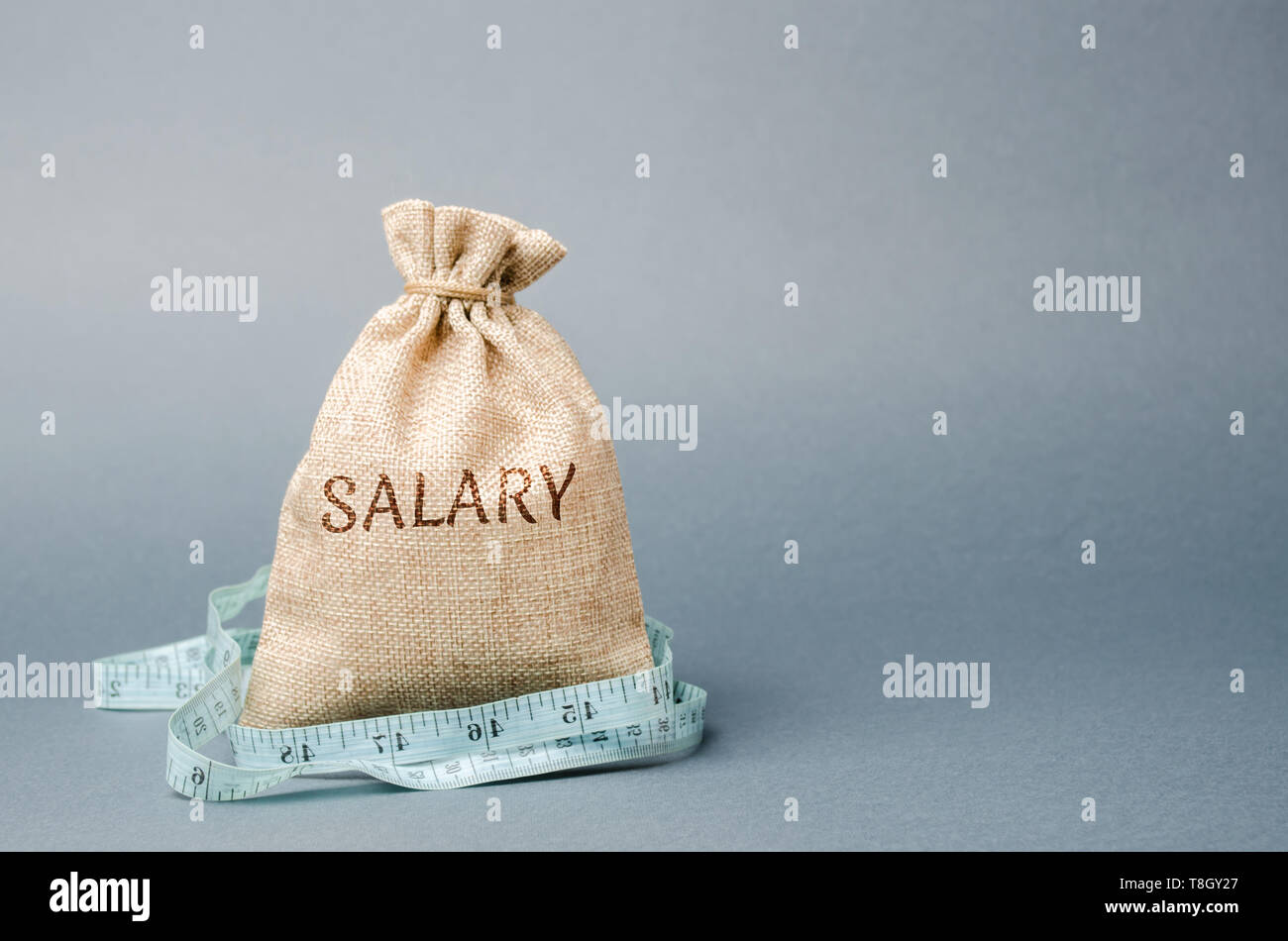 Money bag with the word Salary and tape measure. Wage cuts. The concept of limited profit. Lack of money and poverty. Small income. Salary reduction.  Stock Photo