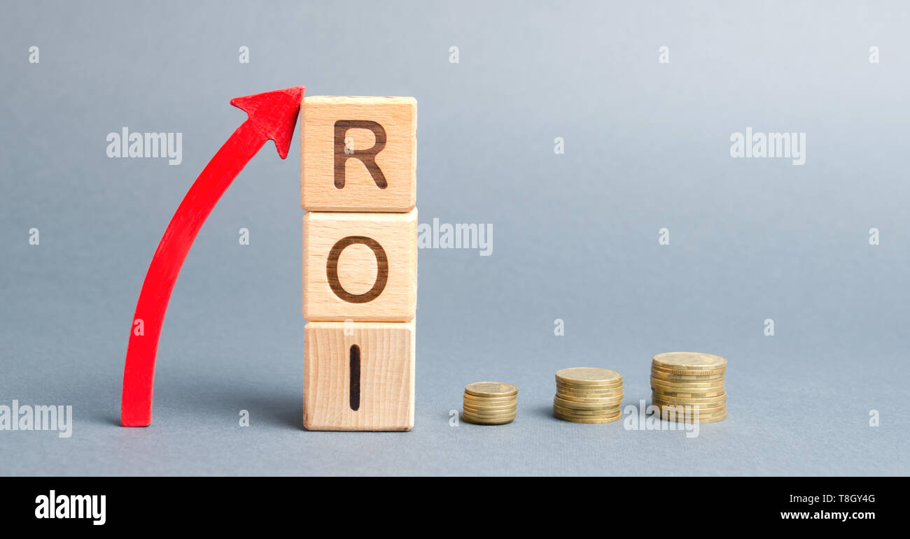 Wooden blocks with the word ROI and arrow up. High level of business profitability. Return on investment, invested capital, rate. Success. Growth. Pro Stock Photo