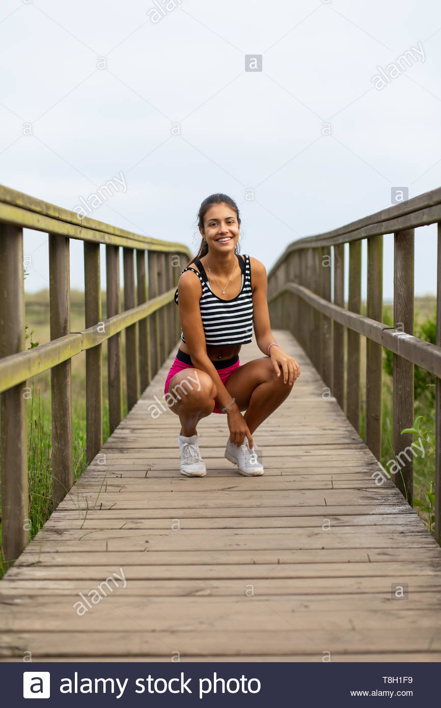 Young sporty woman taking an outdoor running workout rest. Summer fitness lifestyle motivation. Stock Photo