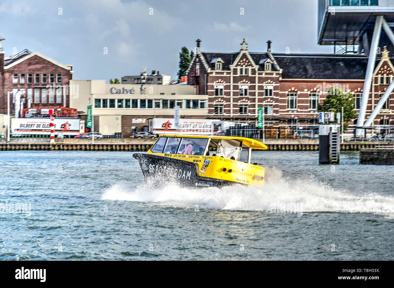 Rotterdam, The Netherlands, August 13, 2018: watertaxi on a curved trajectory on Nieuwe Maas river near Calve factory and Unilever office - Stock Image