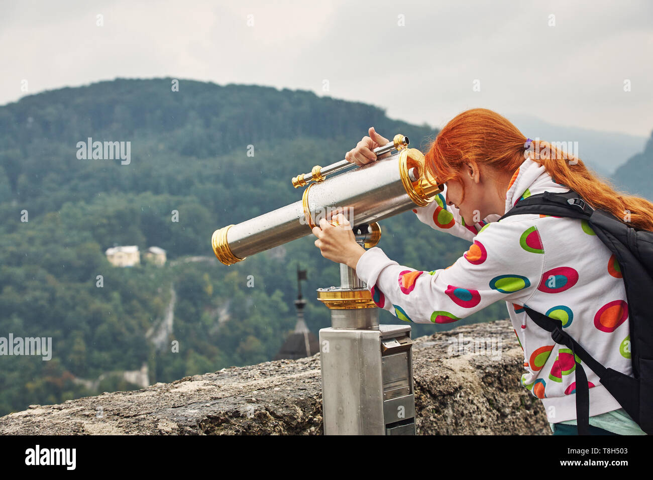Young woman looking through sightseeing telescope a city with an observation deck - Stock Image