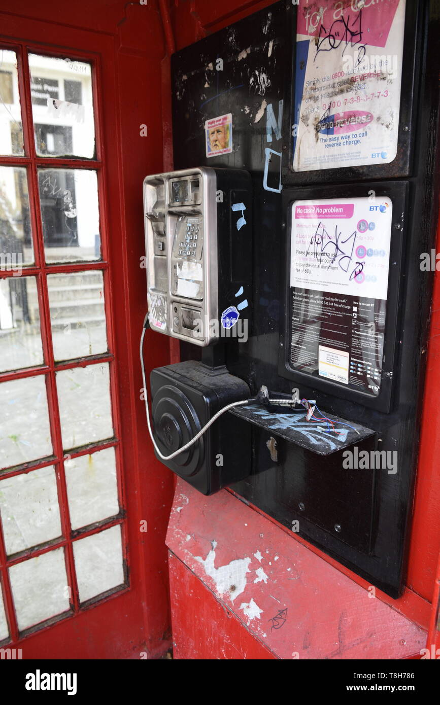 Traditional red London telephone box that has been vandalised, London. - Stock Image