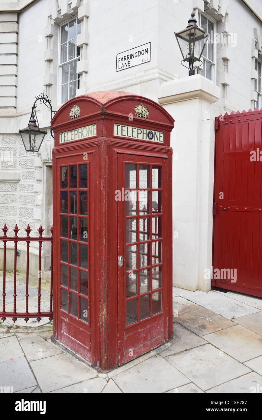 Traditional red London telephone box, next to a red gate. Farringdon Lane, London. - Stock Image