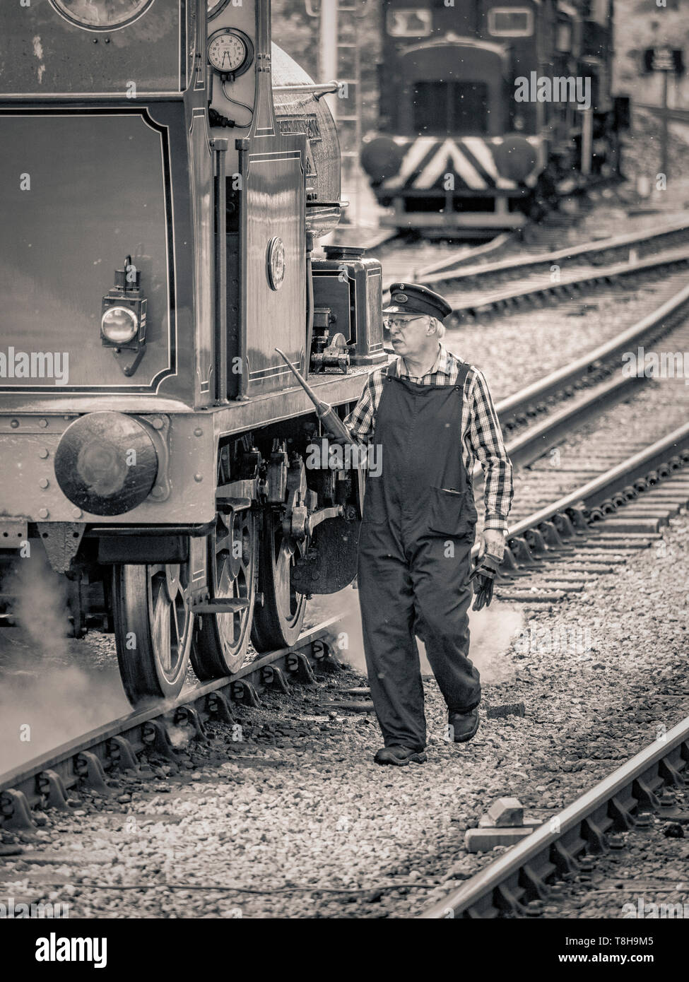 Mechanic working on Sir Robert Alpine and Sons, Engine No. 88. Embsay and Bolton steam railway. Bolton Station, Yorkshire Dales, UK. - Stock Image