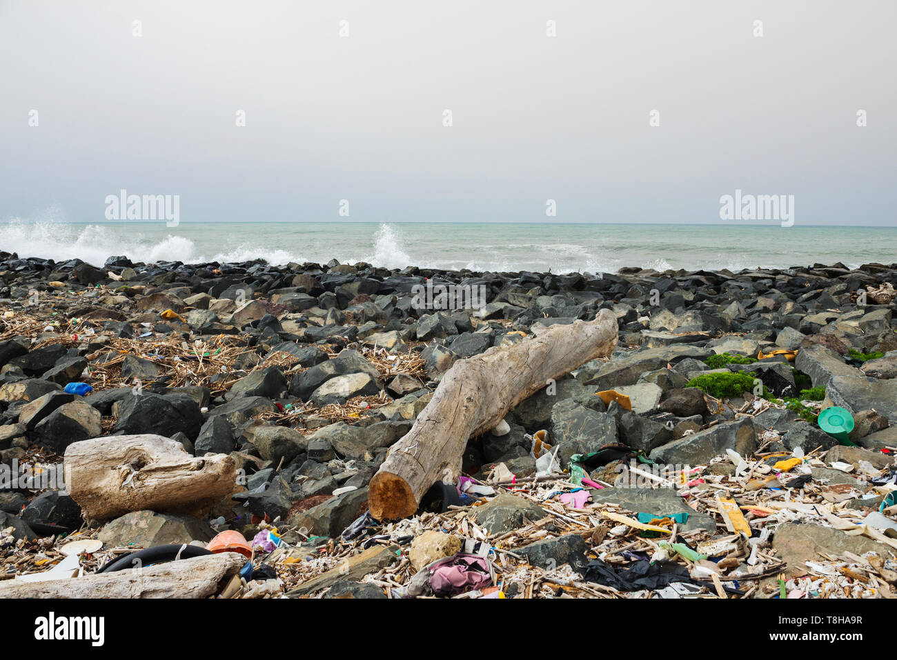 Spilled garbage on the beach near the big city. Empty used dirty plastic bottles and other garbage. Environmental pollution. Ecological problem. - Stock Image