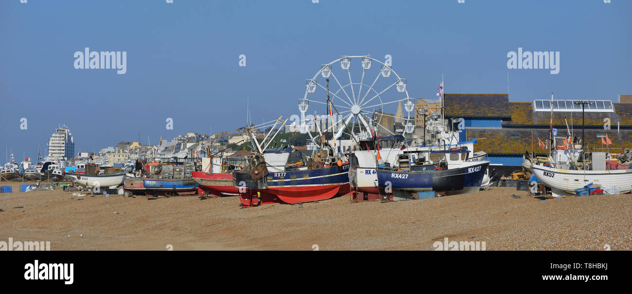 Ferris wheel beside the fishing fleet at the Stade beach, old town, Hastings, East Sussex, England, UK - Stock Image