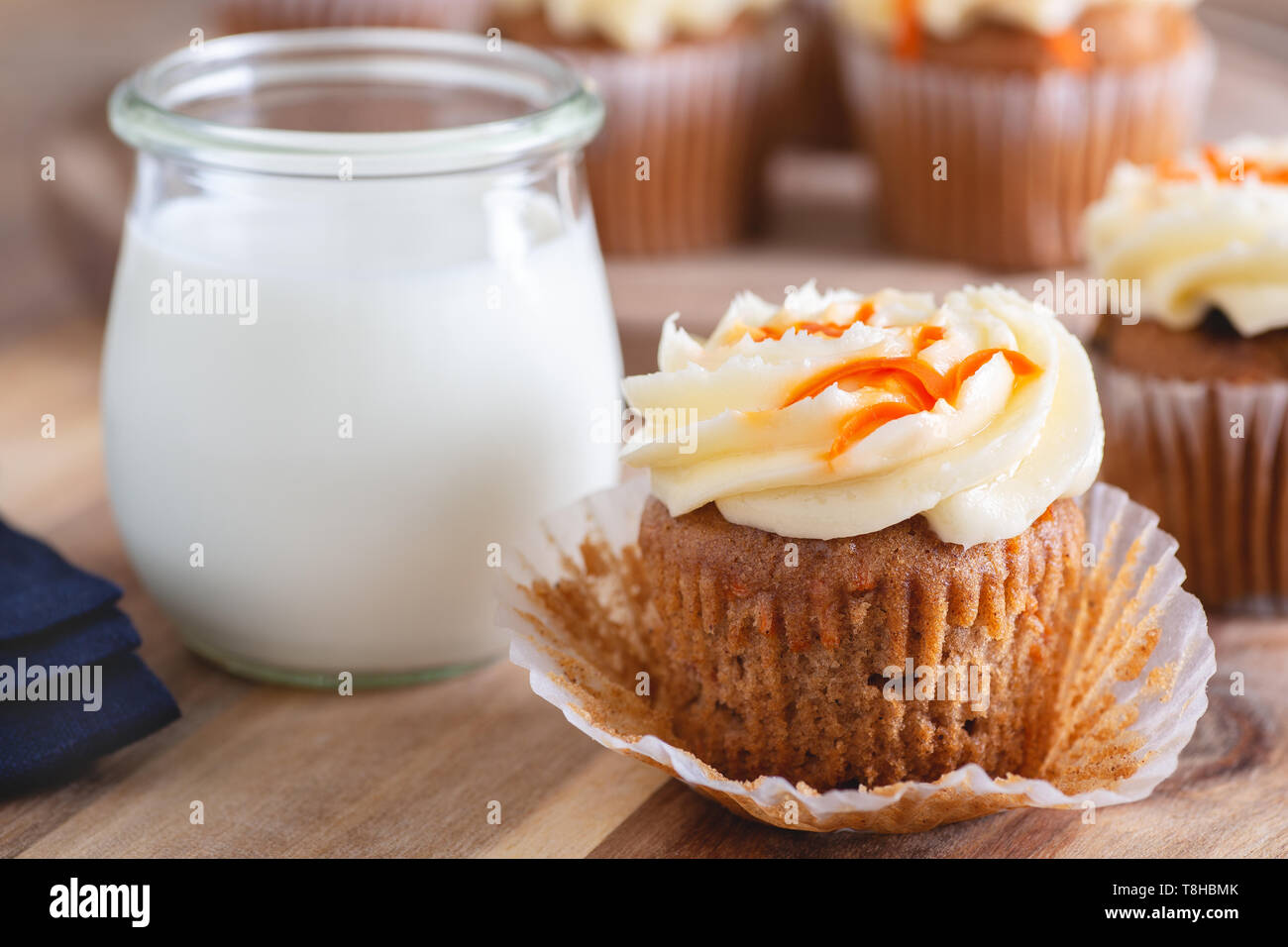 Closeup of carrot cupcake with cream cheese icing and glass of milk and cupcakes in background - Stock Image