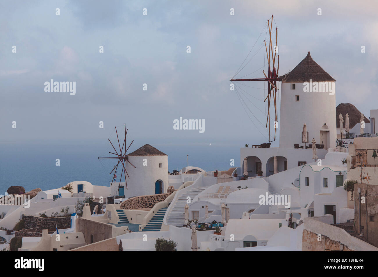 view of the city of Oia, santorini, greece, detail of the mills and the city with typical white buildings, background sea. - Stock Image