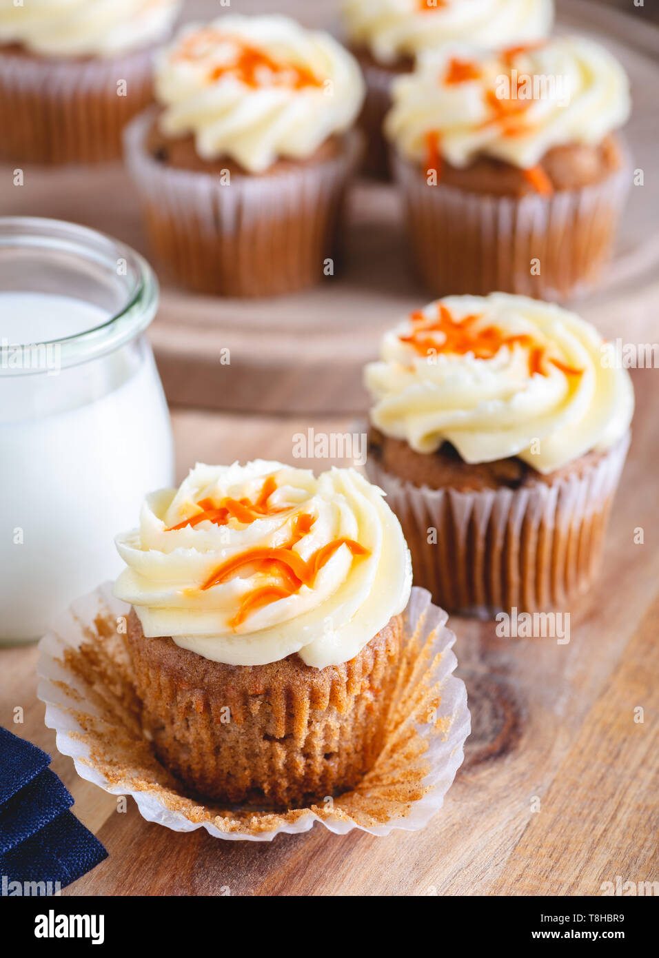 Carrot cupcake with cream cheese icing and glass of milk and cupcakes in background - Stock Image
