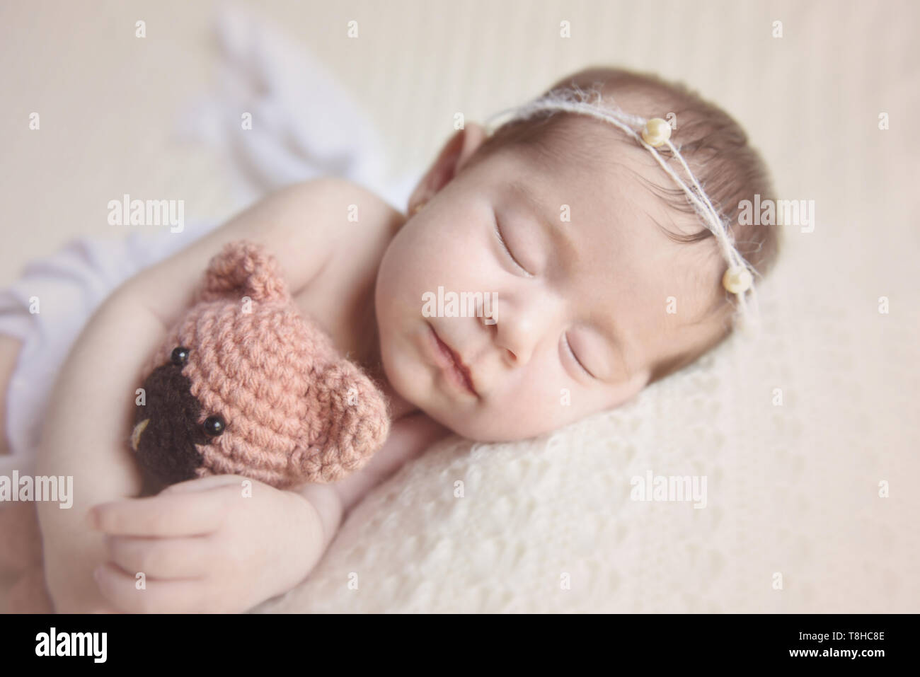 Newborn girl slepping holding a teddy bear - Stock Image