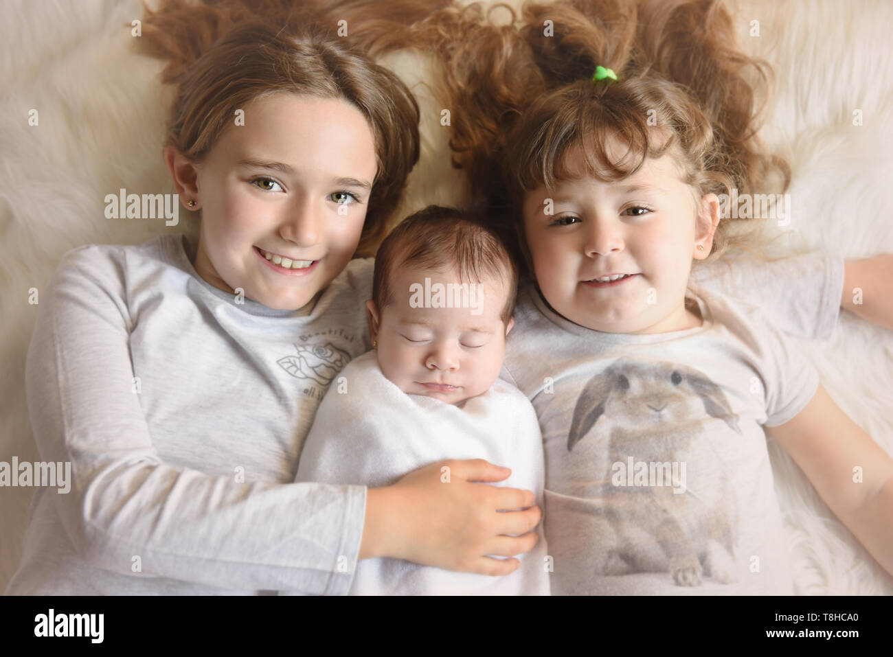 Two pretty sisters holging her newborn sister sleeping - Stock Image
